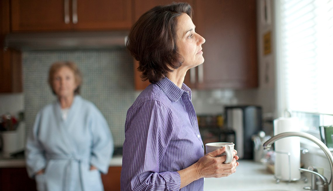 Woman drinking coffee in kitchen, looking sadly out the window. Her elderly mother stands in the background.