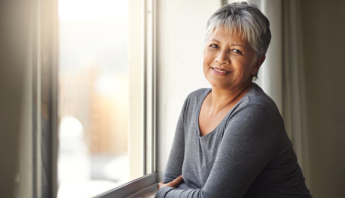 Mujer sonríe en interior de una habitación