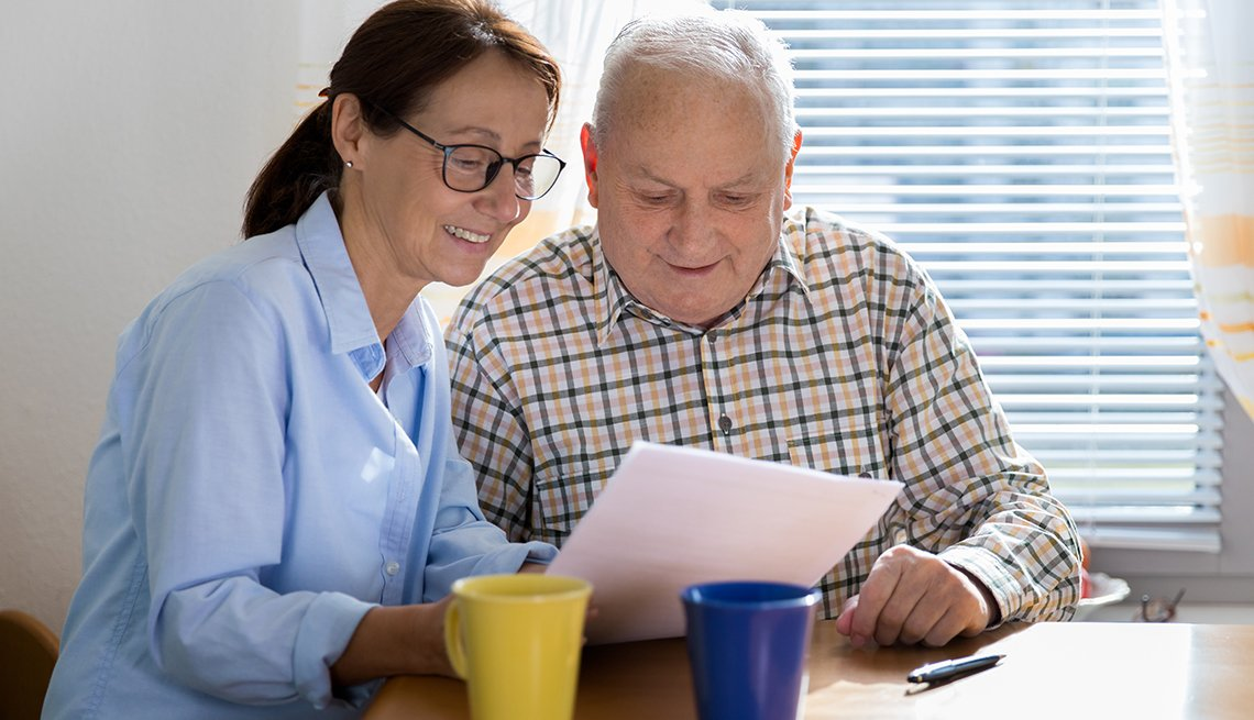 Female caregiver and her father at the kitchen table reading a personal care agreement