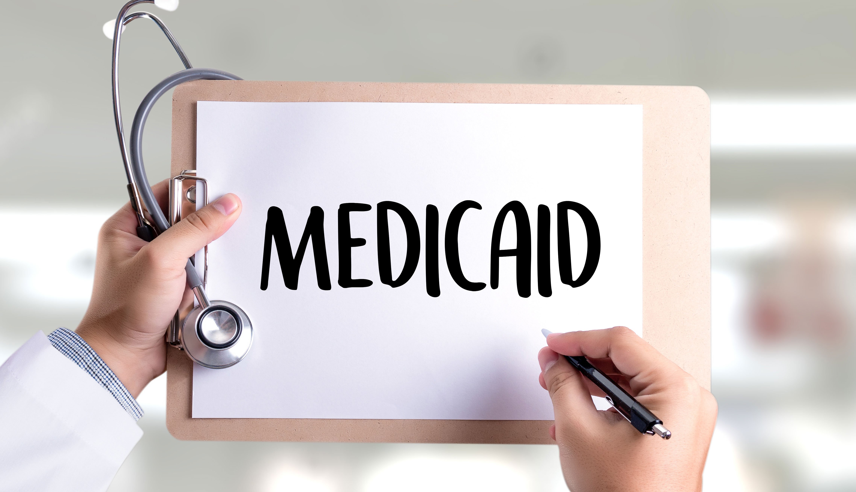 Médico sostiene un portapapeles con un papel que dice Medicaid