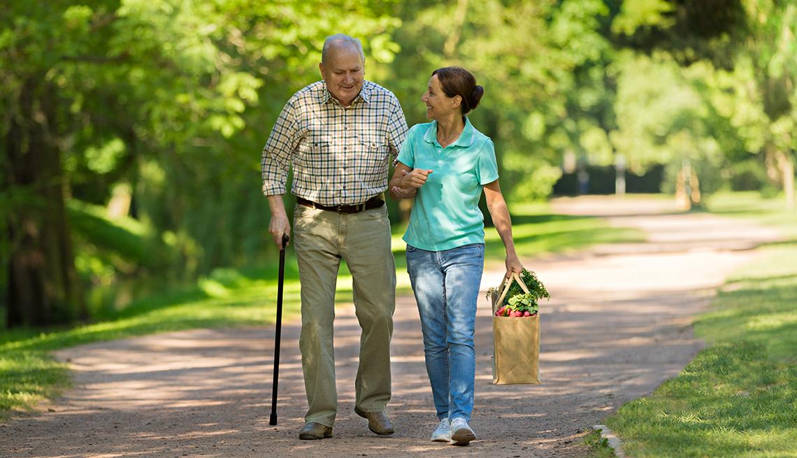 Una cuidadora ayuda a caminar a un hombre mayor