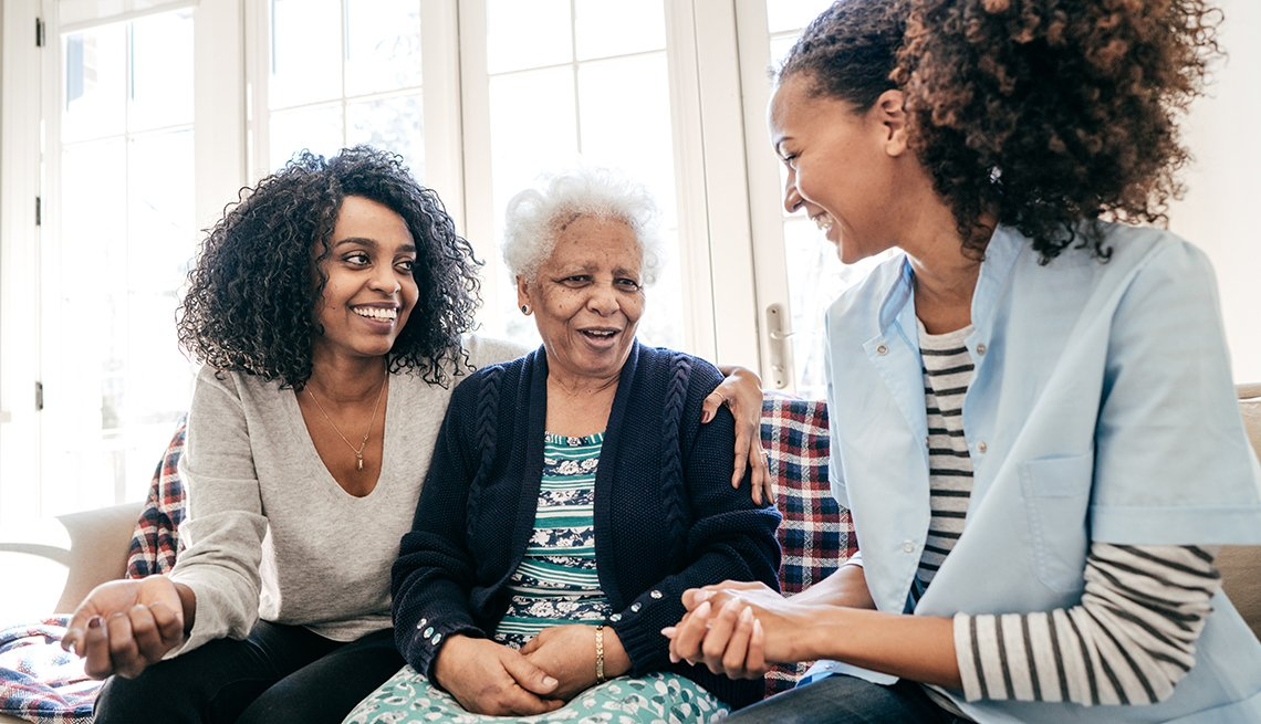 A woman sits on the couch with her elderly mother and a friend