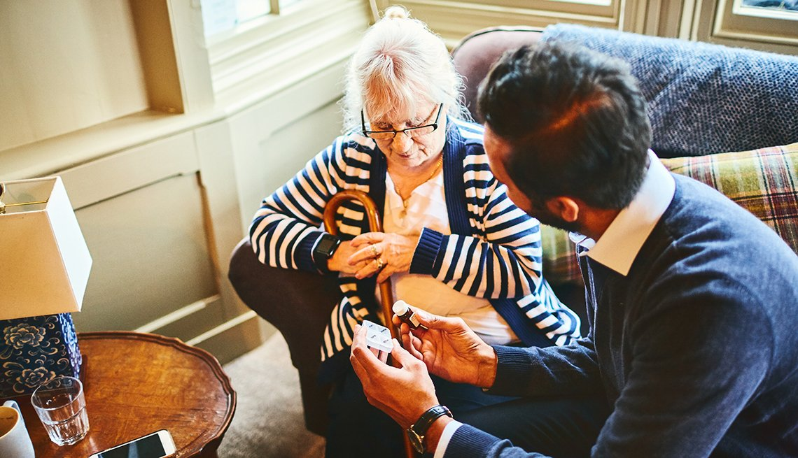 An adult son helping his mother sort out her medications at home