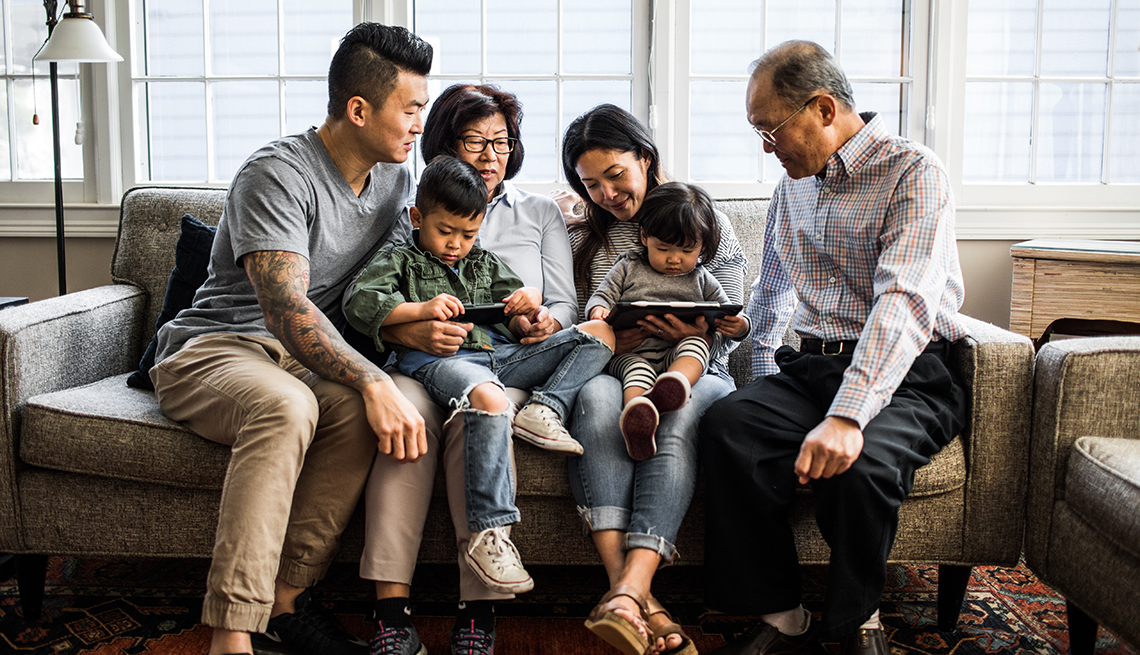 Three generations of family on couch looking at tablet