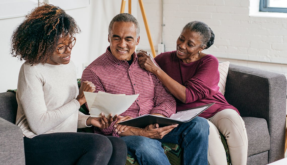 Senior couple reviewing paperwork with their adult daughter