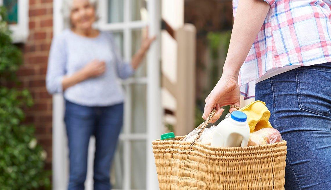 Mujer le lleva una canasta con víveres a una vecina