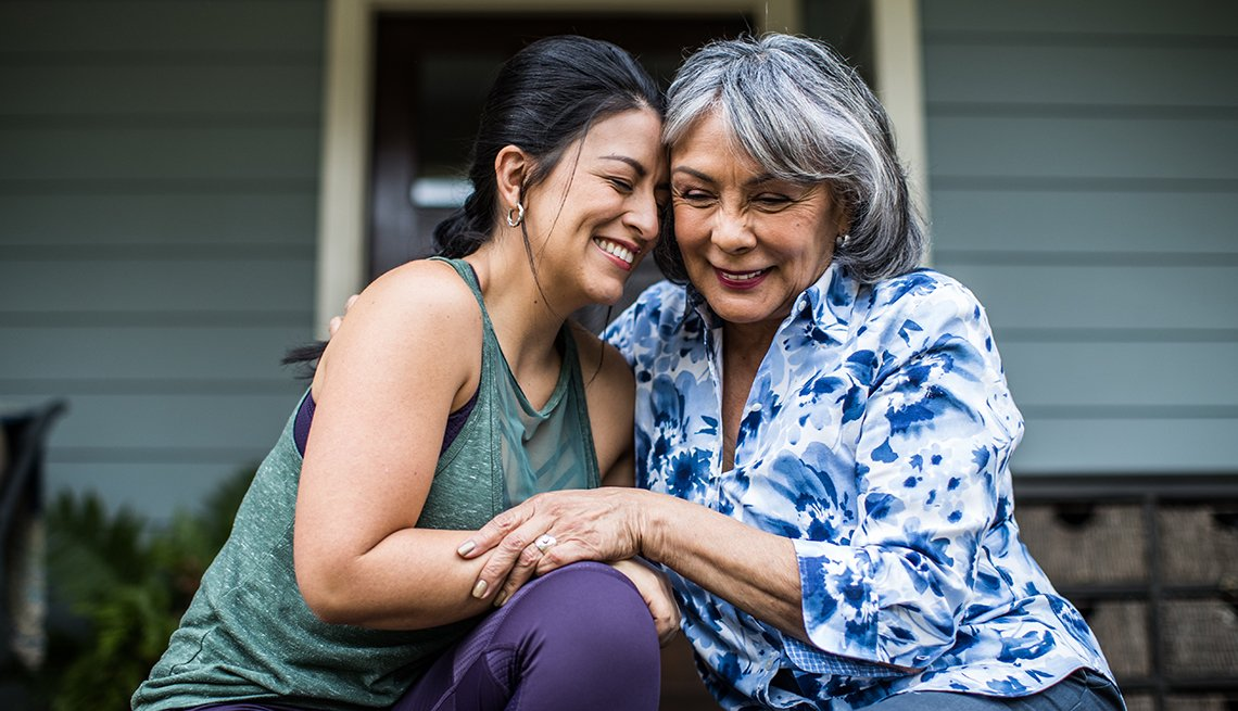 Senior woman and adult daughter embracing and laughing on porch