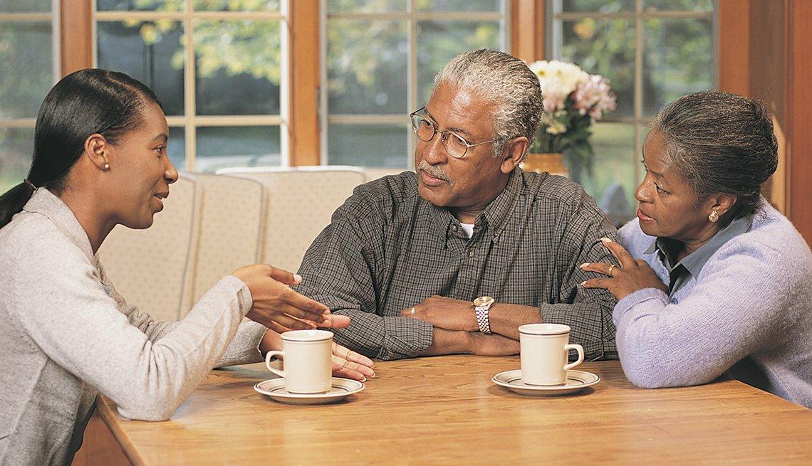 Mujer adulta sentada con sus padres en la mesa de la cocina discutiendo sus planes en caso de una emergencia