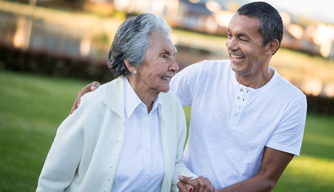 Una mujer camina apoyada de un hombre más joven