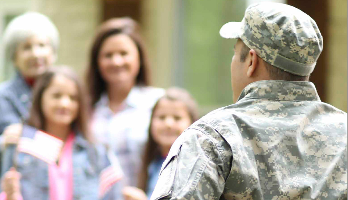 Back of an in military uniform in a wheelchair looking at his family greeting him in the distance