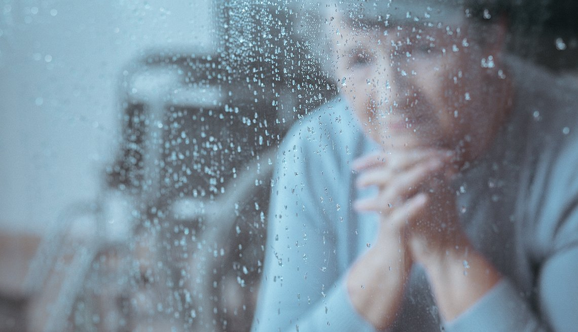 Worried woman looking out a rainy window. A wheelchair is in the background