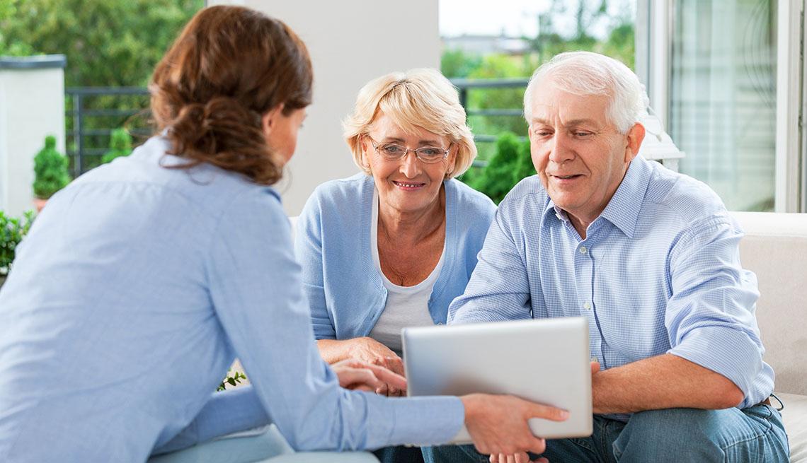 Mujer muestra la pantalla de una tableta electrónica a una pareja de adultos mayores