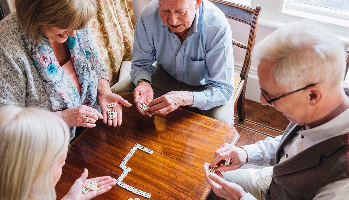 Dos hombres y dos mujeres mayores juegan dominó