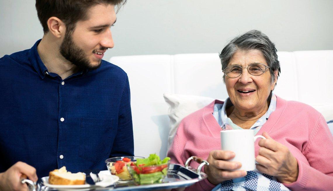 Un joven voluntario sostiene una bandeja con alimentos mientras una mujer mayor tiene una taza en sus manos