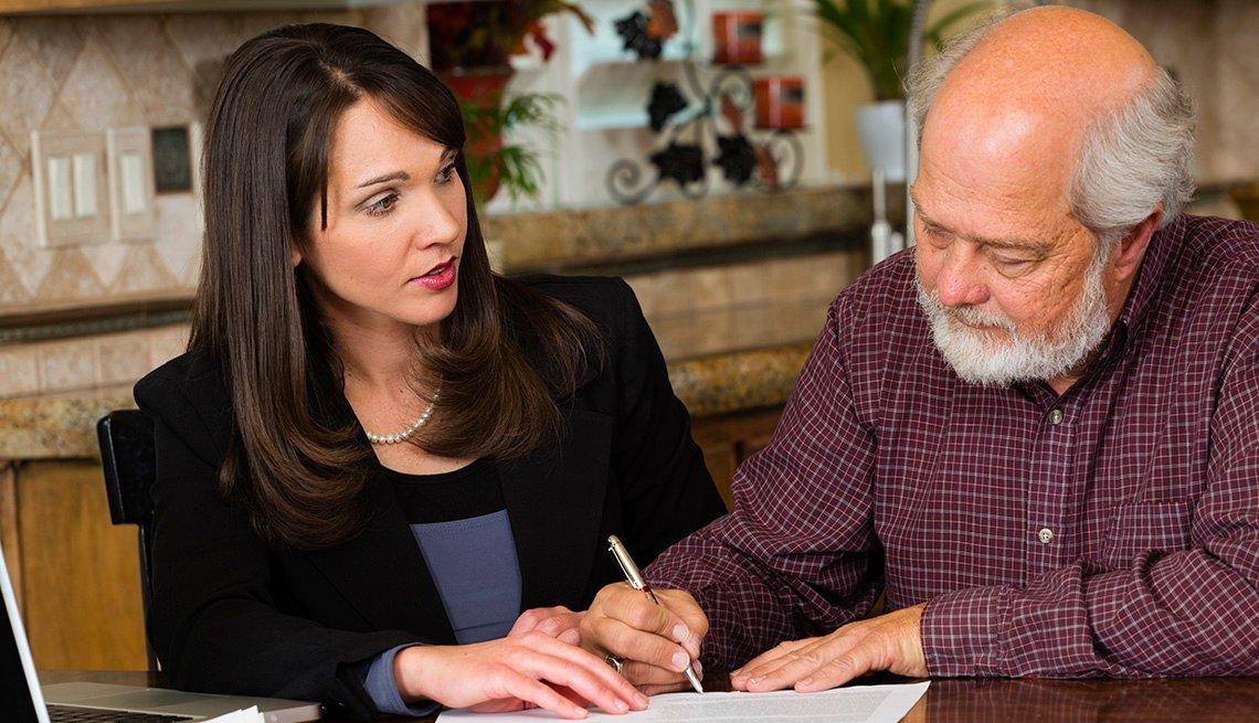 Hombre mayor firma un documento legal en compañía de una mujer joven