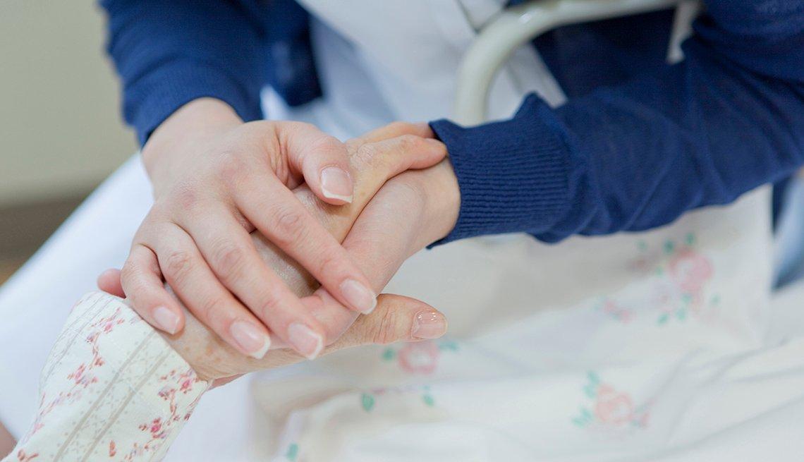 Una mujer sostiene las manos de su madre