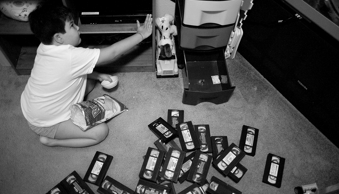 Alex sitting on the floor with bunch of video tapes scattered around him