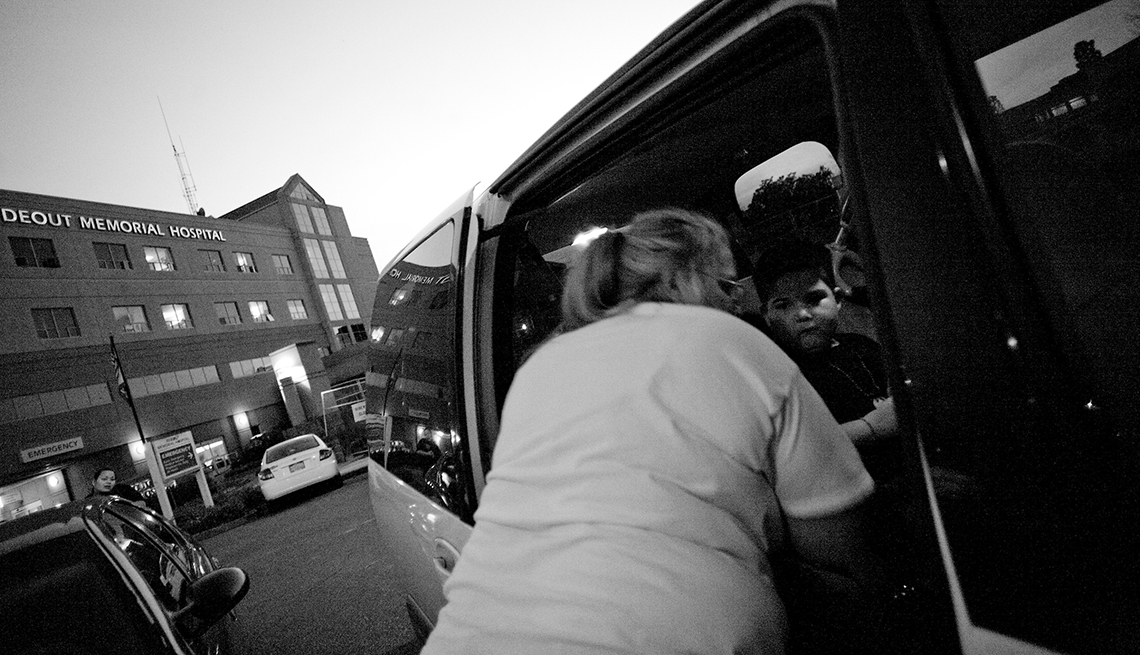 Mary helping Alex into their van after leaving the hospital