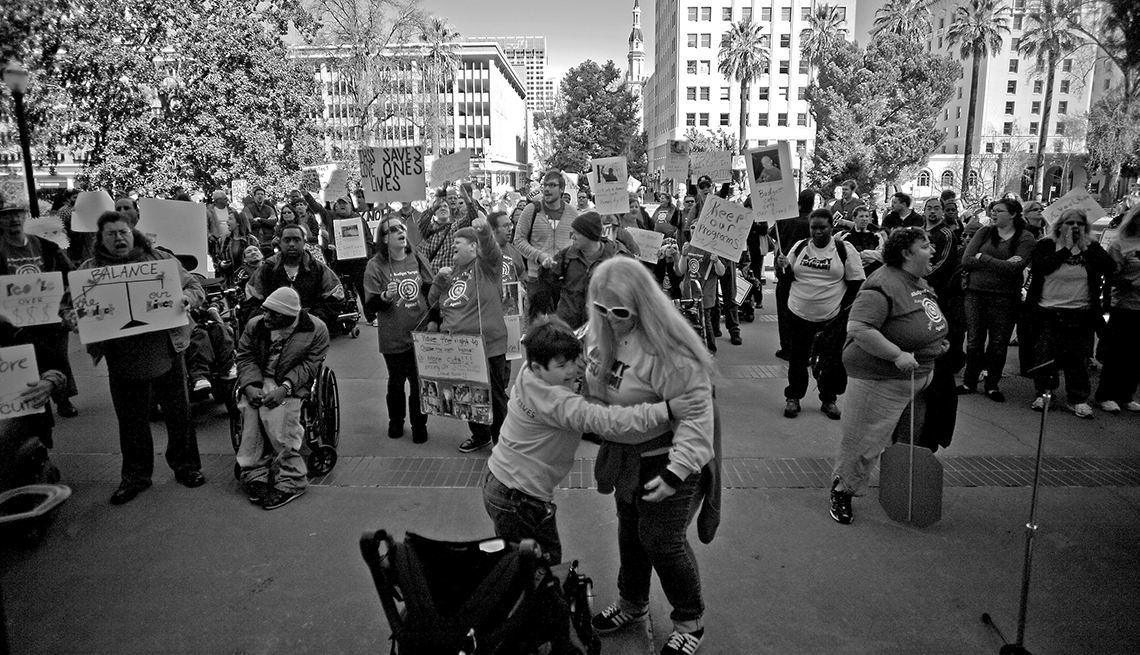 Mary helping Alex out of his wheelchair while marching with hundreds of supporters of disabled rights outside the California state capitol.l