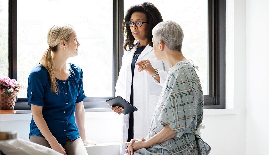 Una doctora habla con su paciente y otra mujer