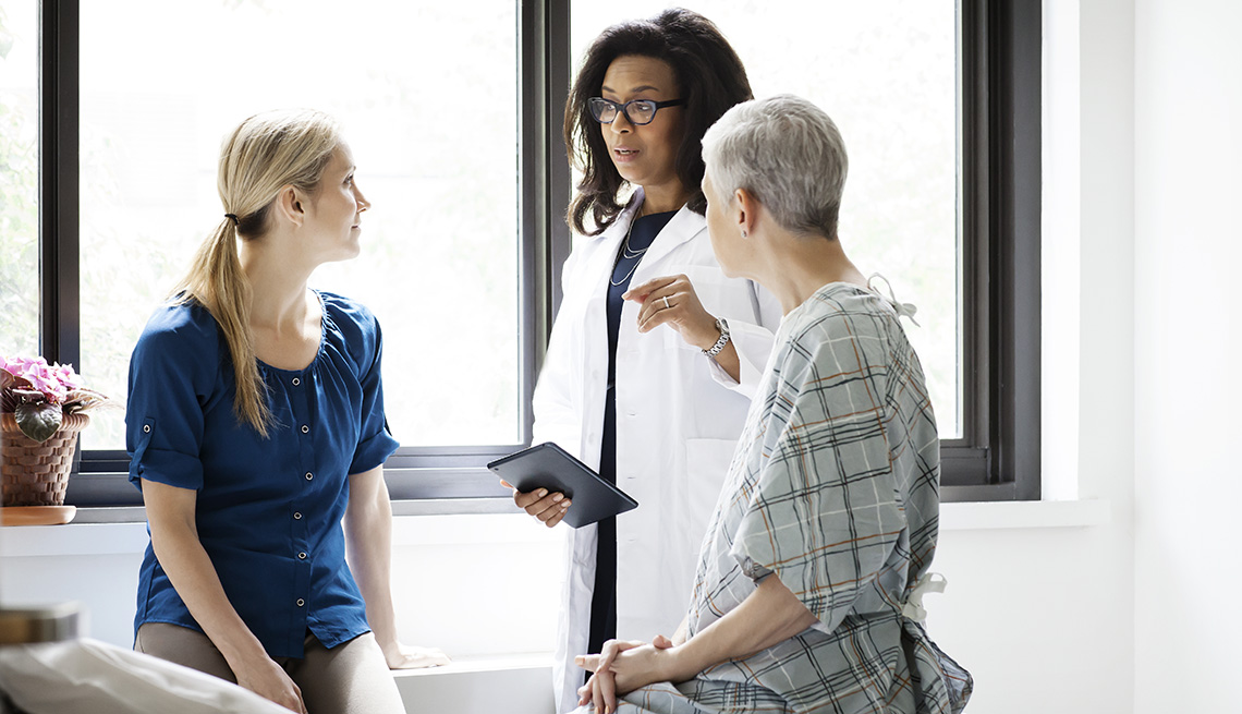 A doctor speaks to a female patient and another woman at hospital