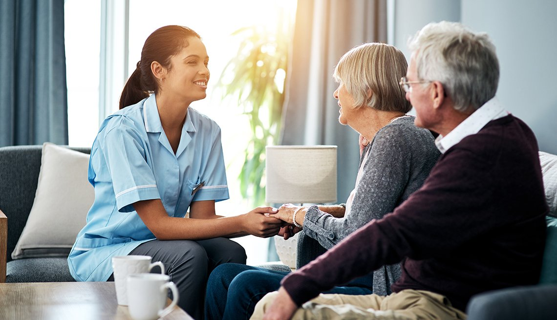 Una enfermera conversa con una pareja mayor
