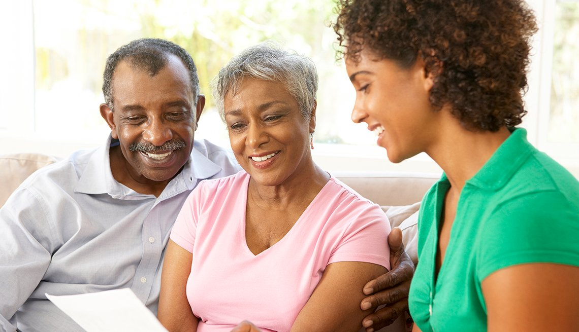 Adult daughter and parents reading through a caregiving guide