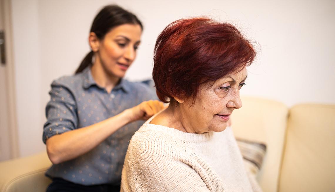 Una mujer joven le da un masaje a una mujer mayor