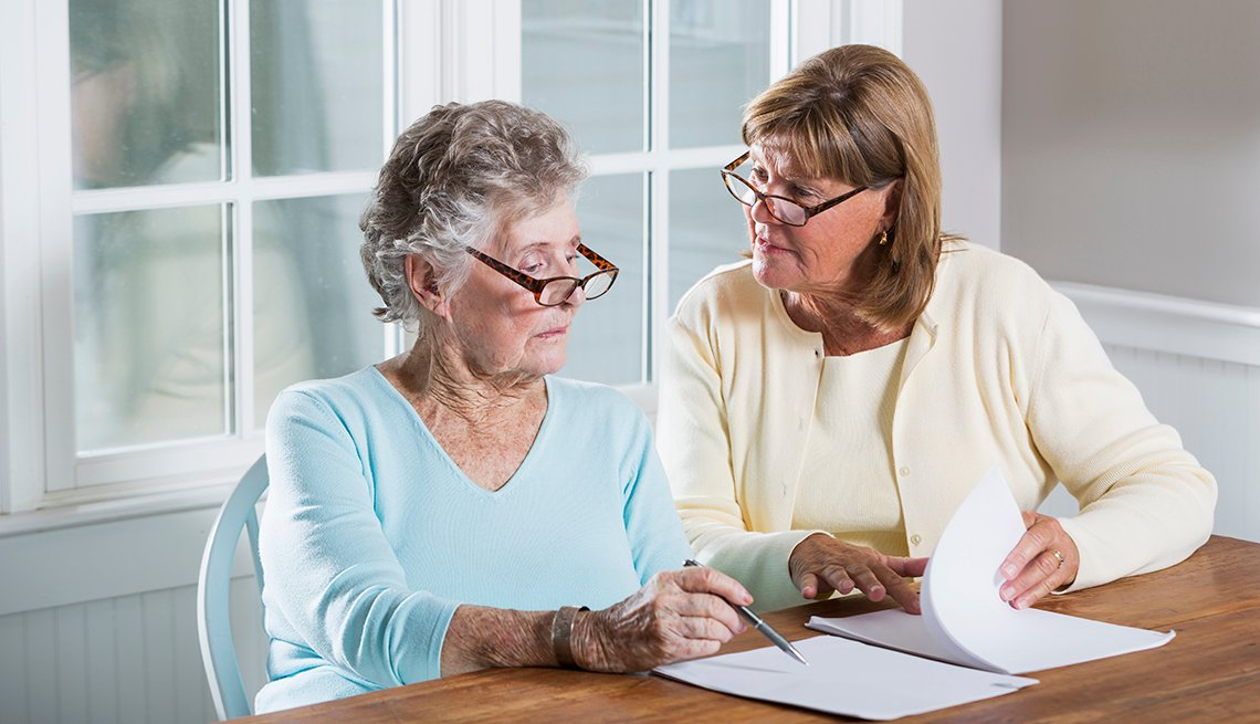 Two women sitting at a table talking about papers that sit before them