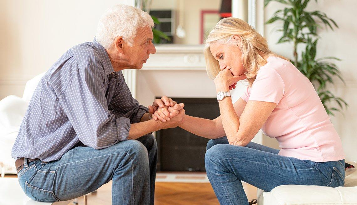 Un hombre consuela a una mujer en la sala de su hogar