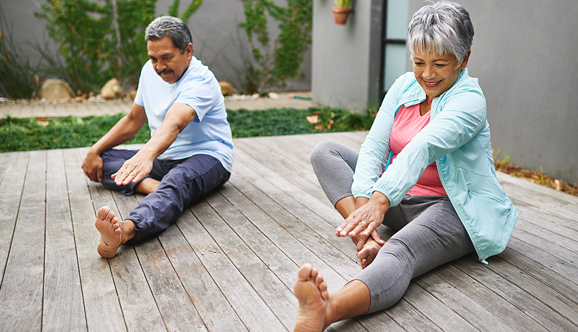 Two older people stretching outdoors