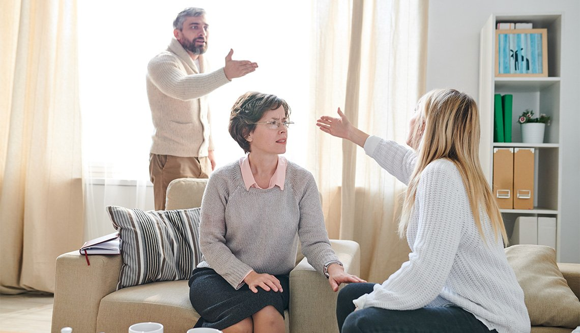 Family psychologist in glasses sitting in armchair and listening to quarrel of couple while asking young lady to stop conflict, emotional couple gesturing hands and blaming each other for their problems