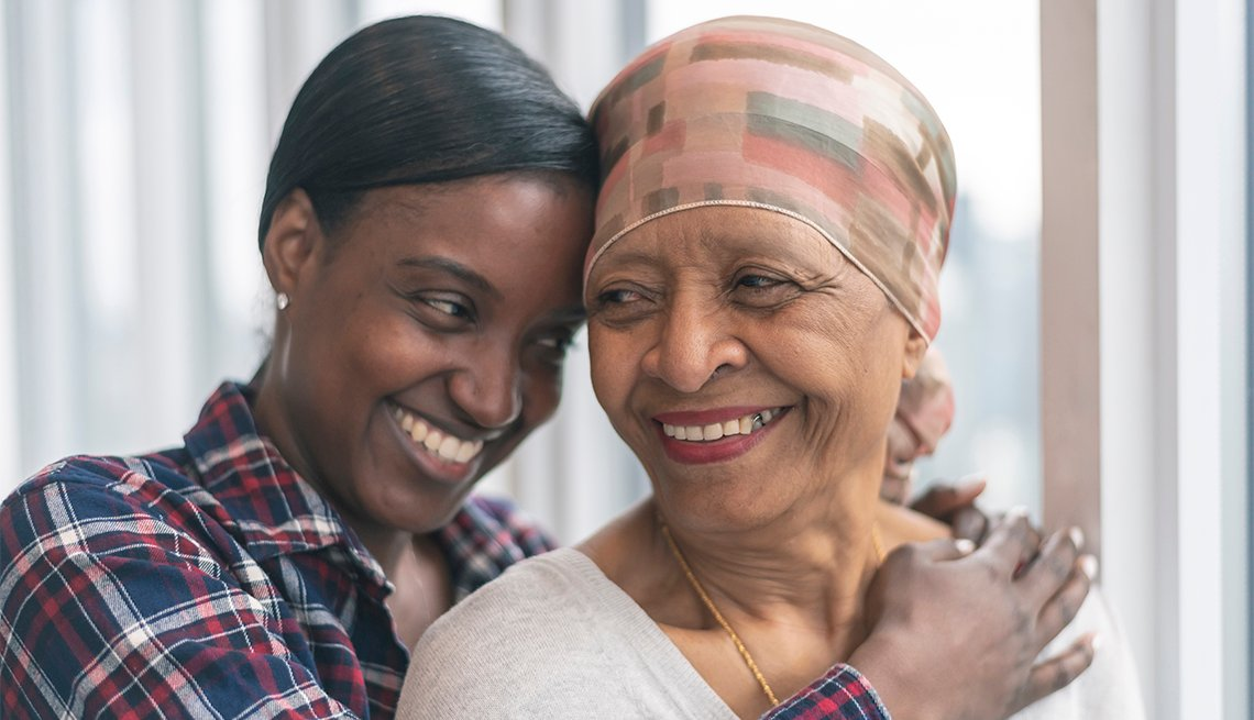 A senior woman with cancer is wearing a scarf on her head. Her adult daughter is giving her a hug. Both women are smiling with gratitude and hope for recovery.