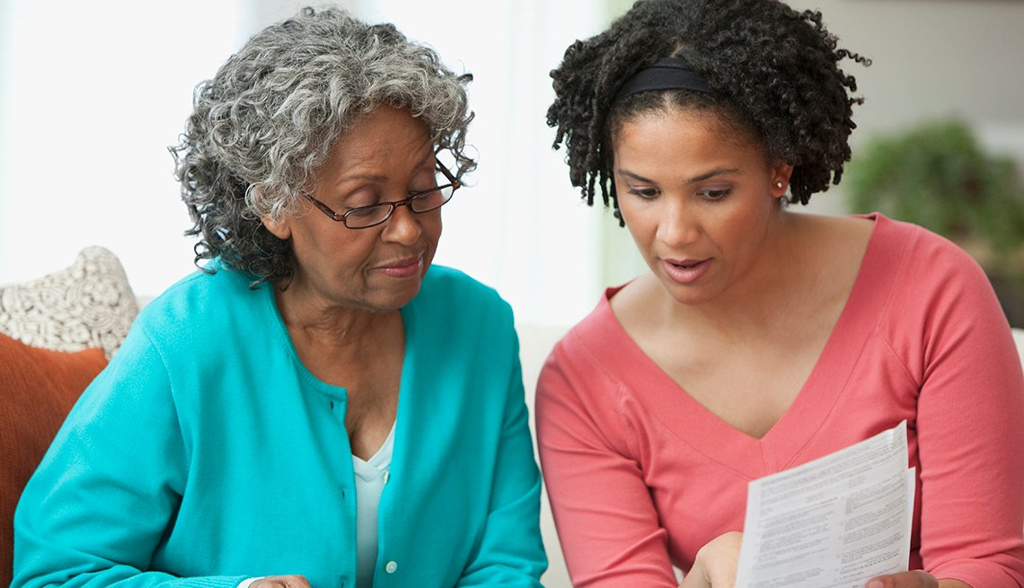 A mother and daughter discussing financial paperwork together