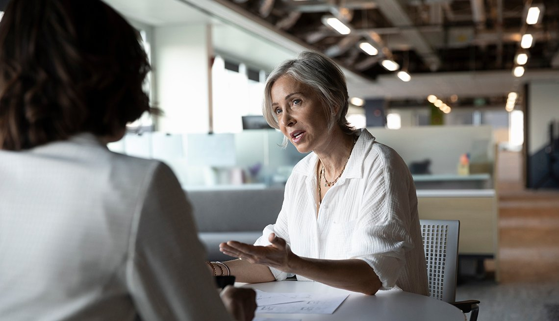 Dos mujeres  conversan en una mesa