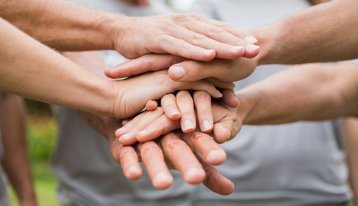 Manos sobre manos en apoyo de grupo