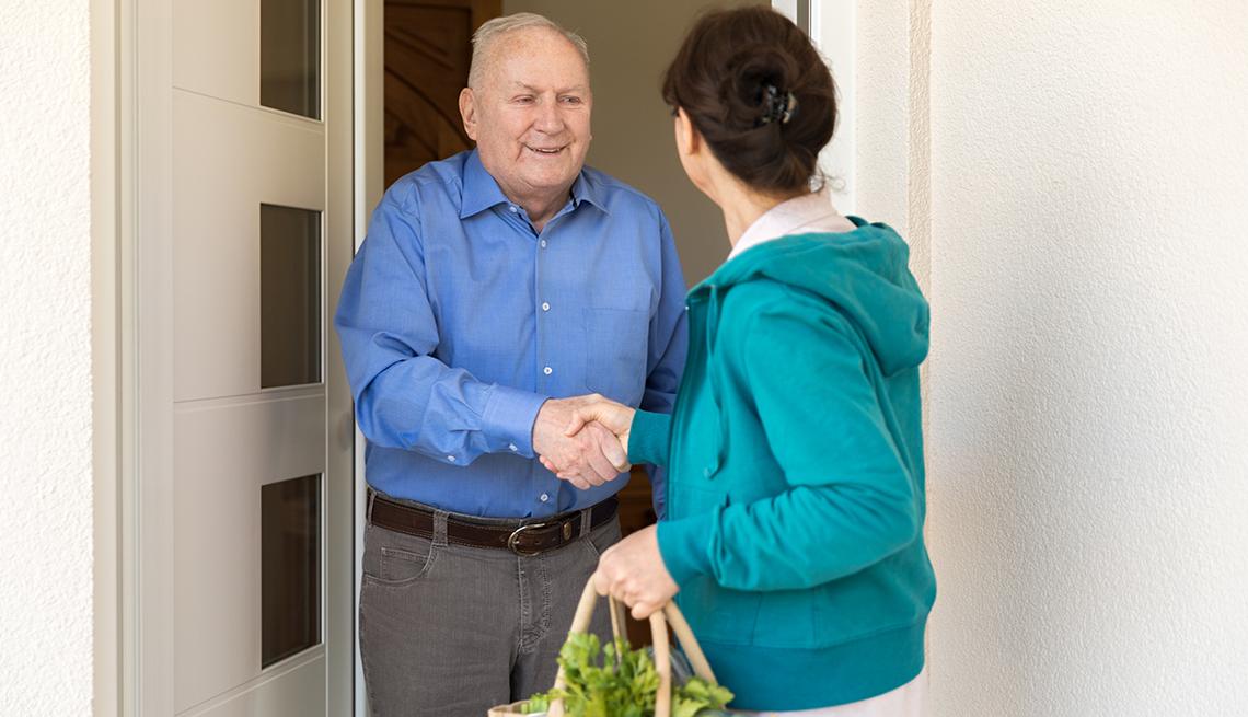 Man at door shaking hand of female caregiver