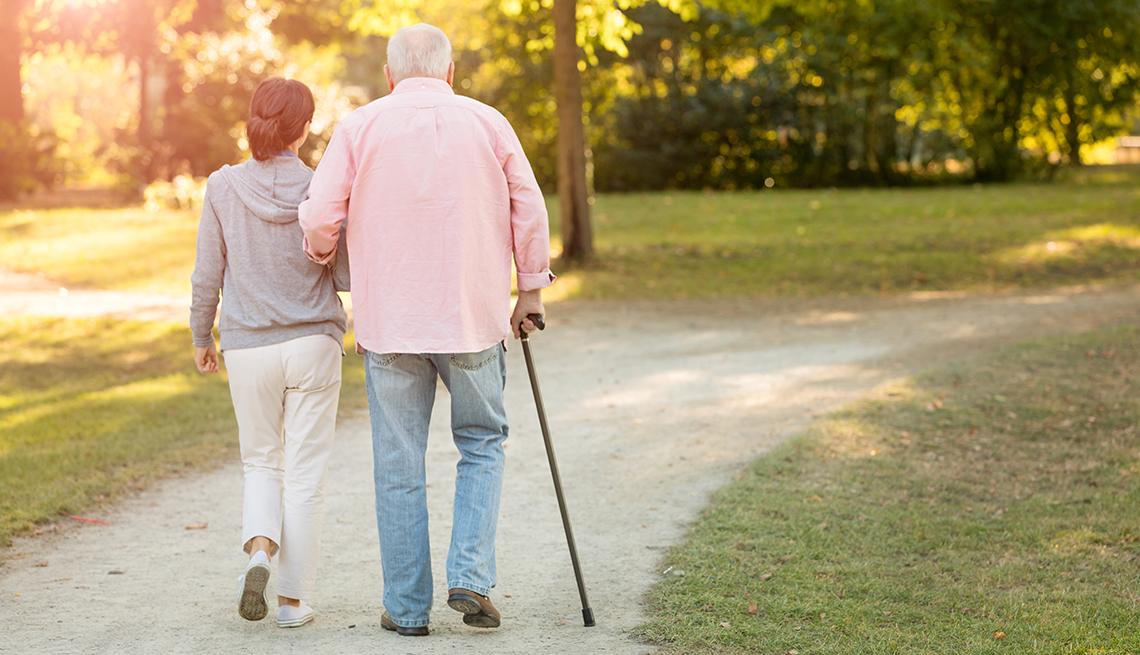 Hombre mayor camina con su bastón y ayudado por una mujer joven