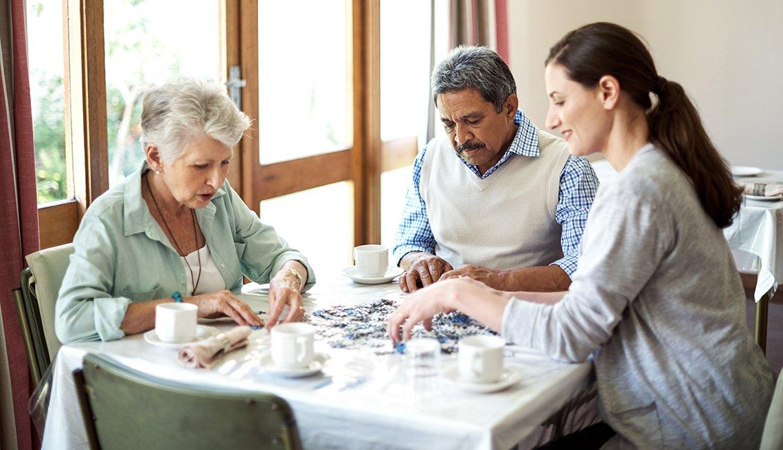 Una enfermera monta un rompecabezas con dos personas mayores