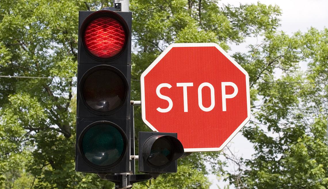 Semáforo en rojo y señal de tránsito que dice stop