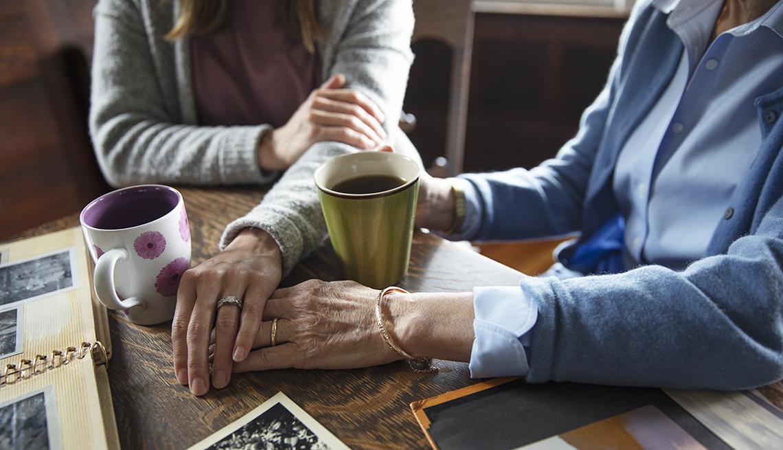 Madre e hija con sus manos juntas, sentadas a la mesa y disfrutan de un café