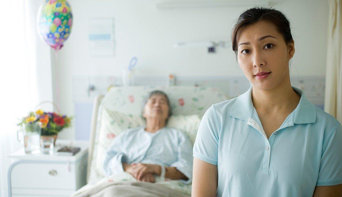 Mujer visita a una mujer mayor en un hospital