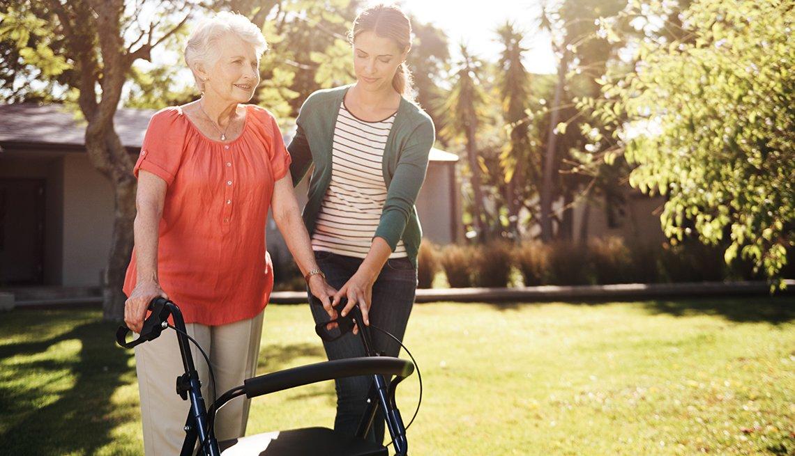 Una mujer mayor usa un andador y una mujer joven la ayuda
