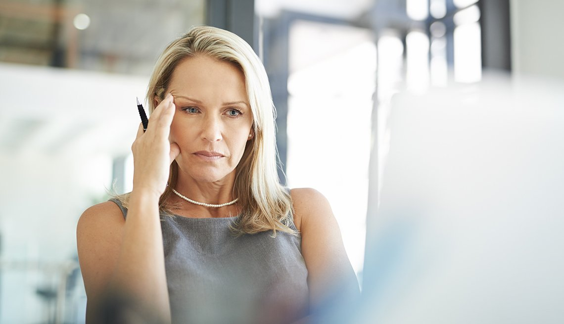 Mature woman looks frustrated while at work