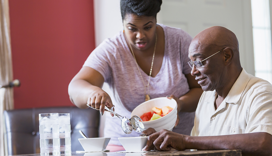 An adult daughter caregiving for her father in his home. She is serving him a bowl of fruit for lunch.