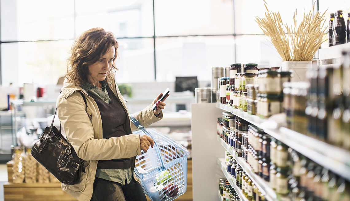 Woman in the vitamin isle of a store holding a phone