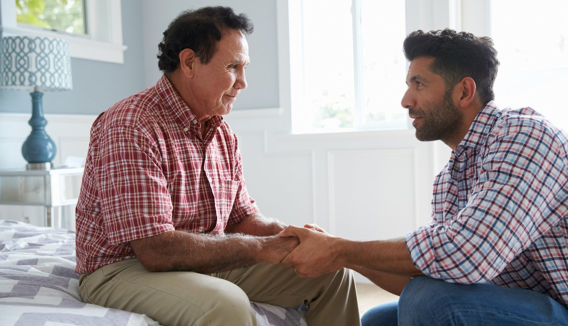 Man with dementia sits on his bed while his adult son comforts him and holds his hands