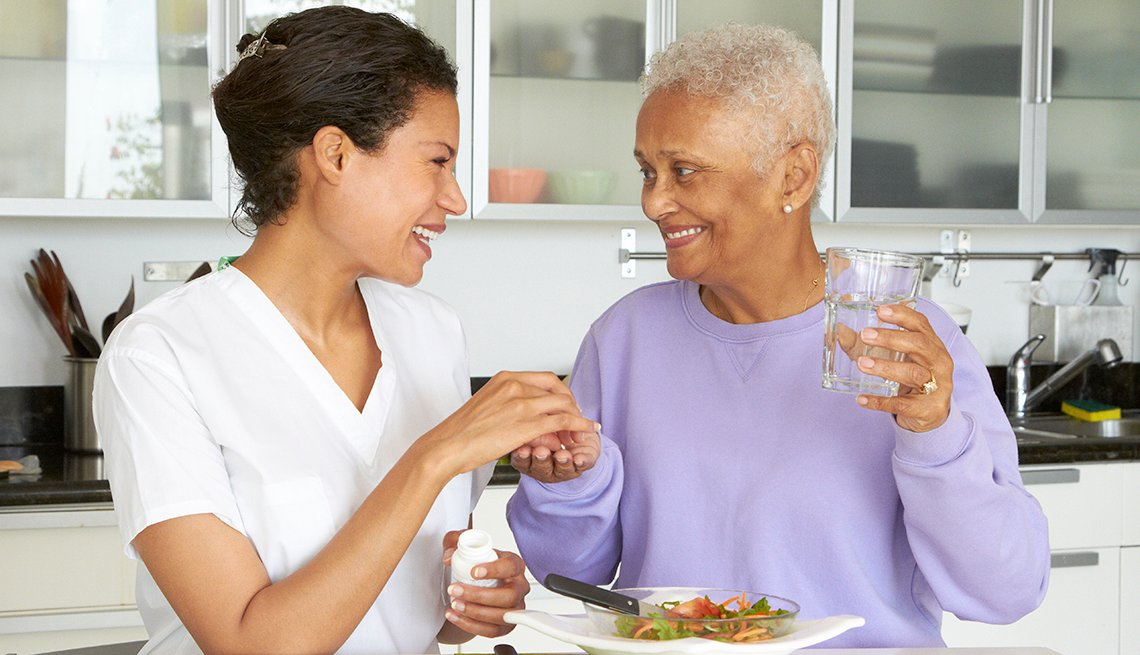 Home health aide giving her female care recipient her pills and a plate of lunch