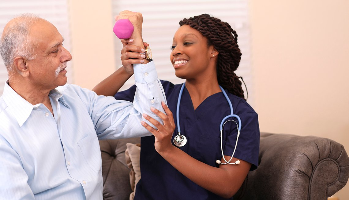 Un hombre mayor hace ejercicios con ayuda de una enfermera