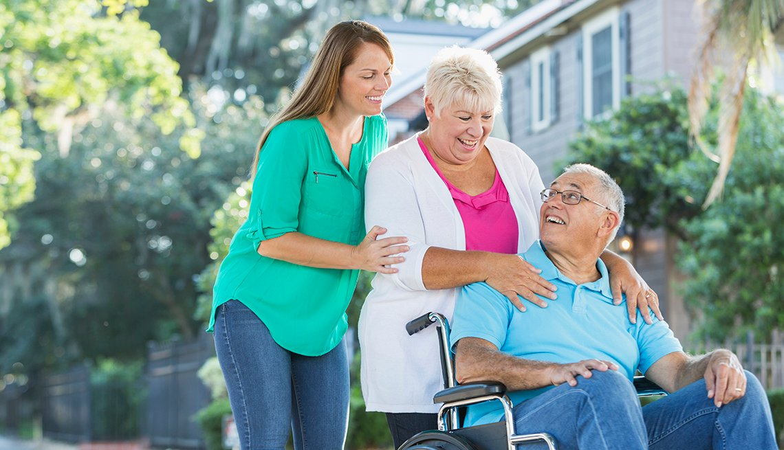 Man is sitting in a wheelchair, his wife standing behind him, hands on his shoulders. Their adult daughter is standing behind her mother